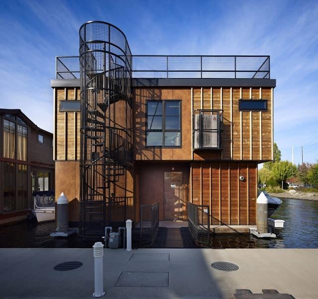 Casa flotante de madera con escalera de caracol exterior.